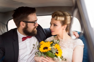 77044452 - young newlywed couple sitting in a retro vintage car, hugging and going away on a honeymoon
